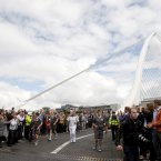 Paul McGrath carries the Olympic Flame over the Samuel Beckett Bridge.