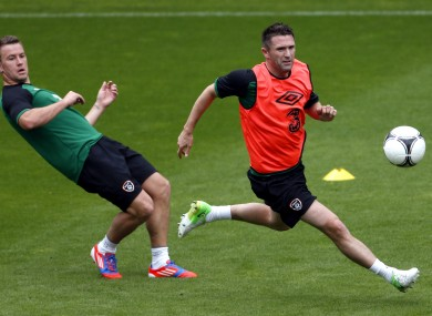 Ireland's Simon Cox, left, and Robbie Keane, right, go for a ball during a training session yesterday.