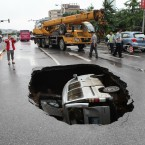 A van is trapped in a hole after a cave-in happened at Fuxing road in Guilin, Guangxi Province of China. The cave-in occurred Tuesday morning after long-term rainfall, injuring the driver. (Photo by He Zhiqin/ChinaFotoPress)