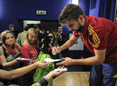 Gerard Pique signs autographs at the Spanish team's base.