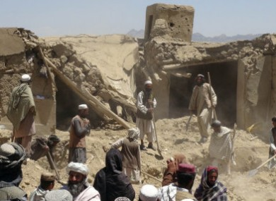 Afghan villagers gather by a house destroyed in the NATO airstrike last week.