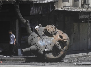 A Syrian man walks next to part of a destroyed military tank on the outskirts of Idlib in Syria