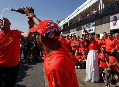 Lewis Hamilton of Britain sprays champagne on McLaren chief  Ron Dennis.