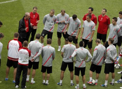 Poland head coach Franciszek Smuda, top left, talks to his players during the official training session yesterday.