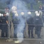 A flare burns behind police officers prior to the Euro 2012 soccer championship Group A match between Poland and Russia in Warsaw, Poland, Tuesday, June 12, 2012. Russian soccer fans clashed with police and Poland supporters in separate incidents in Warsaw on Tuesday, just hours before the two teams were to meet in an emotionally charged European Championship match. Several people were injured. (AP Photo/Alik Keplicz)