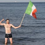 Republic of Ireland fan Emmett MacNamara stands in the sea with an Irish flag in Sopot, Poland.