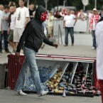 A masked fan walks past a toppled fridge at the Euro 2012 soccer championship Group A match between Poland and Russia in Warsaw, Poland, Tuesday, June 12, 2012. (AP Photo/Gero Breloer)