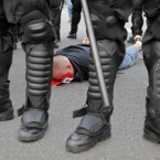 A handcuffed Polish fan sits on the streets prior to the Euro 2012 soccer championship Group A match between Poland and Russia in Warsaw, Poland, Tuesday, June 12, 2012. (AP Photo/Gero Breloer)
