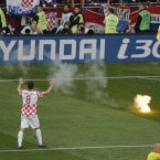 Croatia's Ognjen Vukojevic tries to stop Croatian fans from throwing flares during the Euro 2012 soccer championship Group C match between Italy and Croatia in Poznan, Poland, Thursday, June 14, 2012. (AP Photo/Anja Niedringhaus)