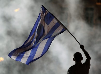 An elderly supporter of New Democracy party waves a Greek flag in front of a smoke from flairs during an election rally at Syntagma square in Athens last night.