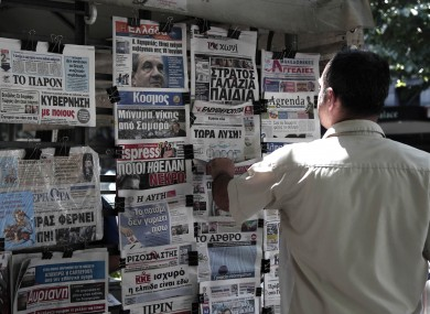 A man looks at the front pages of newspapers in Thessaloniki