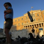 A boy plays with pigeons in front of the Parliament in central Athens. (AP Photo/Petros Karadjias)