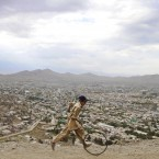 An Afghan boy pushes a wheel on a hill in Kabul, Afghanistan. (AP Photo/Ahmad Jamshid)
