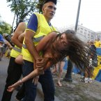 A protester from Ukrainian women rights group Femen is carried away by security guards in the Kiev fan zone during a protest against prostitution prior to the Euro 2012 soccer championship Group D match between Sweden and France in Kiev, Ukraine, Tuesday, June 19, 2012. (AP Photo/Sergei Grits)