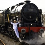 Torchbearer 004 Josephine Loughran carries the Olympic Flame on the Scots Guardsman steam locomotive as they make the journey from York to Thirsk. (PA)