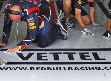 Sebastian Vettel's team members clean the pit lane during the second free session of the first practice day at Valencia street circuit.