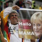 A German fan holds up a poster showing German Prime Minister Angela Merkla before the Euro 2012 soccer championship quarterfinal match between Germany and Greece in Gdansk, Poland, Friday, June 22, 2012. (AP Photo/Thanassis Stavrakis)