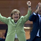 German Chancellor Angela Merkel, left, and German Soccer Federation President Wolfgang Niersbach celebrate during the Euro 2012 soccer championship quarterfinal match between Germany and Greece in Gdansk, Poland, Friday, June 22, 2012. Germany won 4-2. (AP Photo/Gero Breloer)