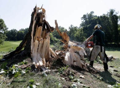 A man uses a chainsaw to clear a storm-felled tree from a golf course in Bethesda, Maryland today.