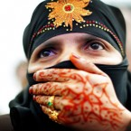 Muhamudda Khadun, a Burmese citizen with traditional henna tattoos, watches Burma's pro-democracy leader Aung San Suu Kyi after receiving the Freedom of the City of Dublin at a special outdoor concert. Image: Julien Behal/PA Wire/Press Association Images