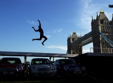 Current British long jump champion J.J. Jegede is silhouetted as he performs an exhibition jump over three Mini cars backdropped by Tower Bridge in London