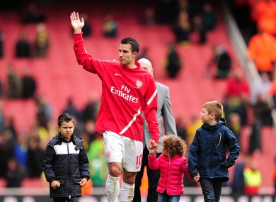 Arsenal's Robin van Persie waves to the crowd as he walks around the pitch with his children after Arsenal's last home game of the season.