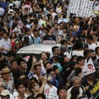 A taxi is surrounded by protesters as tens of thousands of Hong Kong residents march at a down town street (AP Photo/Vincent Yu)