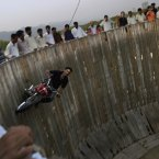 Mohammed Iqbal, 41, rides his motorcycle around a circular vertical track in an entertainment park in Islamabad, Pakistan. (AP Photo/Muhammed Muheisen)