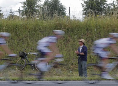 An elderly man, his bicycle parked in the ditch, watches the pack speed by during the fifth stage.
