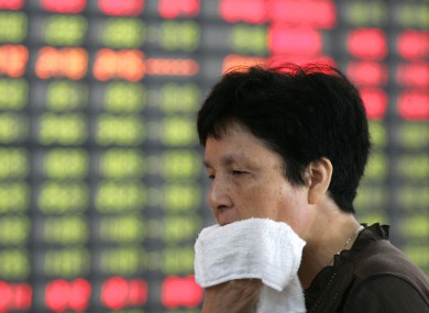 An investor looks at a stock price monitor in Shanghai, China last week.