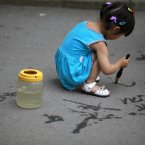 A little girl uses a brush dipped in water to practice Chinese calligraphy at a park in Shanghai. (AP Photo/Eugene Hoshiko)