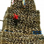 A man climbs one of the biggest bonfires at New Mossley on the outskirts of Belfast. ( Paul Faith/PA Wire)