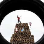 A man stands on top of one of the biggest bonfires (Photo: Paul Faith/PA Wire)
