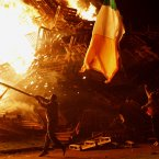 Residents throw the Irish flag onto the Shankill bonfire (AP Photo/Peter Morrison)