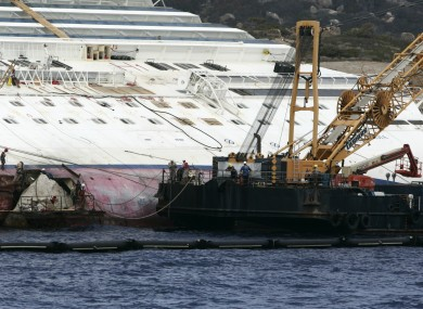 Workers begin to remove the tons of rocky reef embedded into the Costa Concordia cruise ship's hull earlier this month.