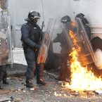 Riot police come under attack from a petrol bomb thrown by nationalist rioters (AP Photo/Peter Morrison)