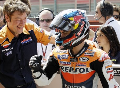 Honda rider Dani Pedrosa of Spain reacts after clocking the fastest time to take the pole position.