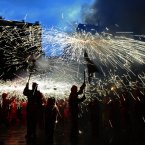 Revelers hold torches as they take part in 'Correfoc' party in Barcelona, Spain,. Correfocs or