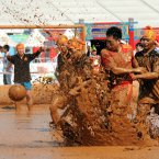 Players scuffle in the mud at a match of swamp soccer during the Swamp Soccer China 2012, held outside the National Stadium, better known as the Birds Nest in Beijing, China. (Photo by ChinaFotoPress)