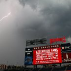 A bolt of lightning comes down from the clouds near Nationals Park before a baseball between the Washington Nationals and the New York Mets. (AP Photo/Alex Brandon)