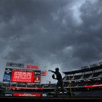 New York Mets relief pitcher Miguel Batista warms up in the rain before a baseball game between the Mets and the Washington Nationals on Wednesday. (AP Photo/Alex Brandon)