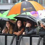 Fans wait in the rain at the Echo Arena in Liverpool to watch the Boot Camp performances in this year's series of the X Factor. (David Richards: Optimus Images Ltd)