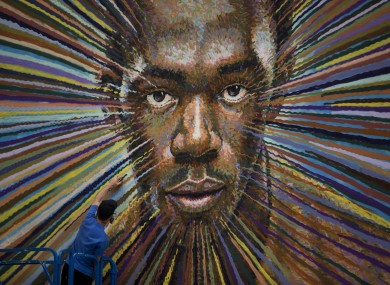 Australian street artist James Cochran spray paints a portrait of Usain Bolt, Jamaica's world record holder in the 100 and 200 meter sprints, on the wall of a building beside a car park in east London.