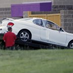 The car belonging to the suspect in the mass shooting at the Century 16 theatre east of the Aurora Mall, is loaded on to a flatbed truck. (AP Photo/David Zalubowski)