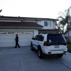A San Diego police officer stands in front of the home of the mother of Colorado shooting suspect James Holmes. (AP Photo/Gregory Bull)