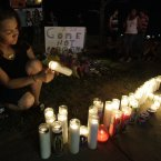 Esmeralda Carbajal lights candles at a growing memorial across the street from the Century 16 movie theatre. (AP Photo/Ted S. Warren)