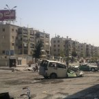 This citizen journalist image shows Syrians walking past destroyed vehicles after fighting between rebels and Syrian troops in the Yarmouk camp for Palestinian refugees in south Damascus, Syria, Saturday, July 21, 2012. (AP Photo)