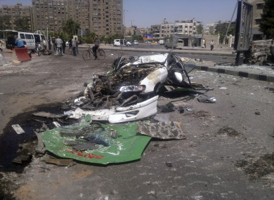 This citizen journalist image shows a destroyed car on a street damaged by tank treads after fighting between rebels and Syrian troops in the Yarmouk camp for Palestinian refugees in south Damascus yesterday.
