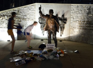 People visit the Joe Paterno statue before its removal from the Penn State campus on Sunday morning.