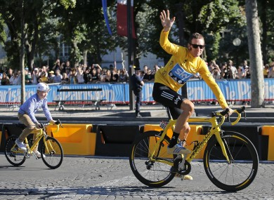 Wiggins cycling race rides up the Champs Elysees with his son during a parade after the last stage of the race in Paris.
